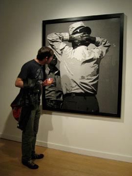 Gilson inspects a photograph of a paper cut by Vik Muniz (Rena Bransten Gallery)
