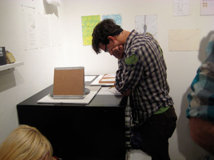 A viewer reads N. Sean Glover's instructions for the cardboard record player.