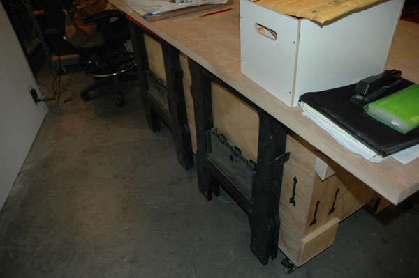 Free crate + casters + door + sawhorses = two tables that fold into one. Genius.