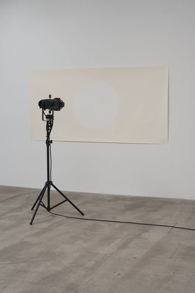 Amalia Pica, Under the spotlight (white on white), 2011. Installation with spotlight, motion sensor, paper and paint. Source: MarcFoxx.com.