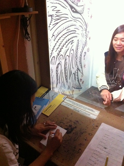 Drawing in the Sketch-O-Mat. Sitters drop a suggested donation of £1 for a 5-minute portrait.