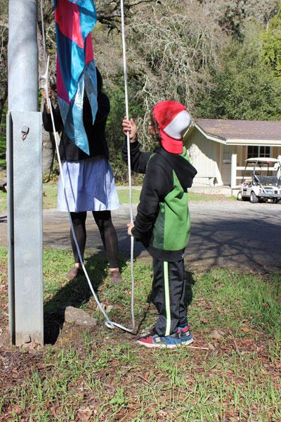 The littlest volunteer hoists the flag.
