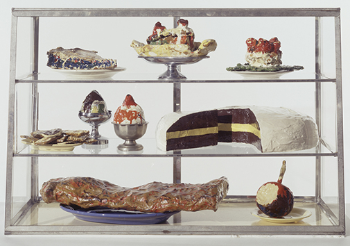 "Claes Oldenburg. Pastry Case, I 1961—62 Burlap and muslin soaked in plaster, painted with enamel, metal bowls, and ceramic plates in glass-and-metal case. 20 3/4 x 30 1/8 x 14 3/4"" (52.7 x 76.5 x 37.3 cm). The Sidney and Harriet Janis Collection. © 1961—62 Claes Oldenburg. Photo: The Museum of Modern Art, Imaging and Visual Resources Department, Kate Keller. // Source: moma.org."