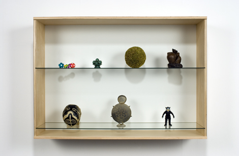 Haim Steinbach, Untitled (skull, vessel, figurine, toy, fruit bowl, sphere, peasant), 2006  Birch plywood, plastic laminate and glass box; synthetic polymer skull; Korean ceramic vessel; plastic figurine; plastic baby toy; Chinese fruit bowl; straw ball; Chinese ceramic statuette 37-3/4 x 53-3/4 x 14-3/4 in. (95.8 x 136.6 x 37.5 cm) // Source: HaimSteinbach.net.