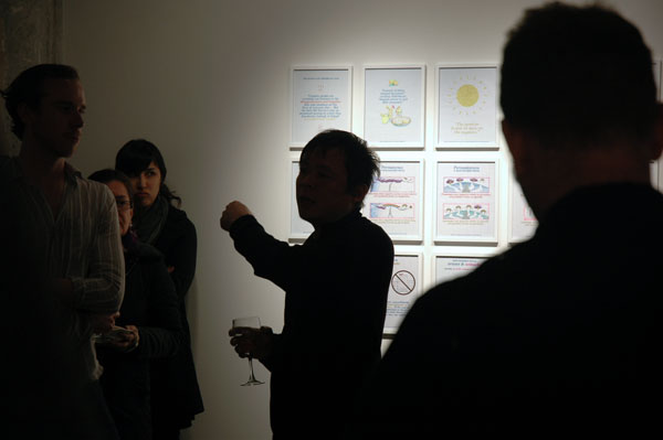 "Backlit curator Kevin Chen speaks at the opening of ""In Other Words,"" 2012. my Positive Signs drawings are on the wall behind him."