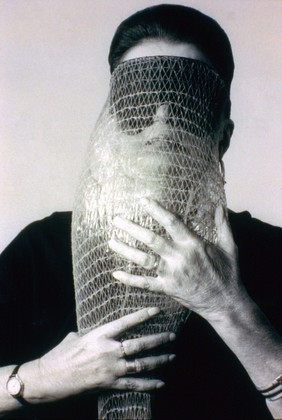 "Lygia Clark wearing Máscara abismo com tapa-olhos (Abyssal mask with eye-patch, 1968), a work made of fabric, elastic bands, a nylon bag, and a stone, in use. Courtesy Associação Cultural ""O Mundo de Lygia Clark,"" Rio de Janeiro. Photograph: Sergio Gerardo Zalis, 1986 // Source: moma.org."