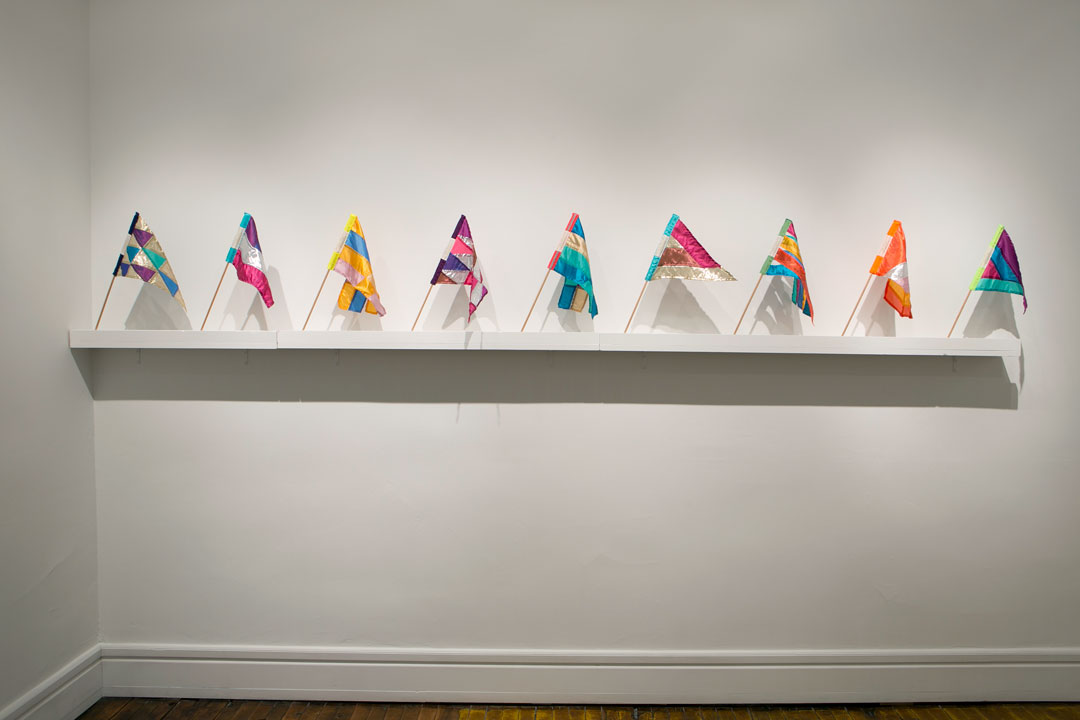 Personal-sized, spirited declarations suggest a semaphore of positive sentiment or unabashed enthusiasm. Christine Wong Yap, Irrational Exuberance (Asst. Colors) Mini Flags, 2012, fabric, thread, wood, woven labels, ~15 x 18 inches / 38 x 45 cm each . Installation view at SideCar Gallery, Hammond, IN. Photo: Clare Britt.