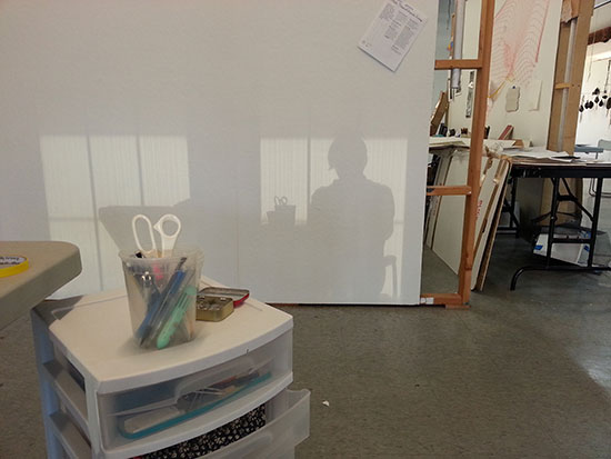 My silhouette on my studio wall, formed in sunset light reflected from skyscrapers.