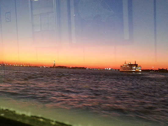 A recent view of the Statue of Liberty at sunset, also with the Staten Island ferry.