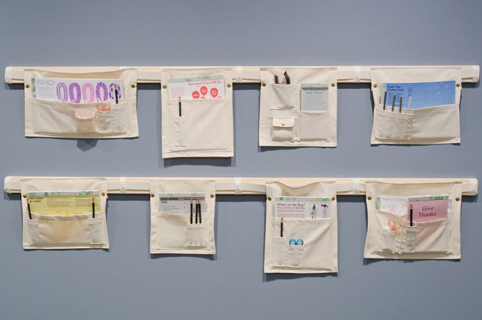 Activities housed in canvas pouches, displayed on a wall. Participants can attach them to garments using the snaps. Supported by a Fellowship from Kala Art Institute and an Artist-in-Residence Workspace Grant from the Center for Book Arts. Photo: Jiajun Wang