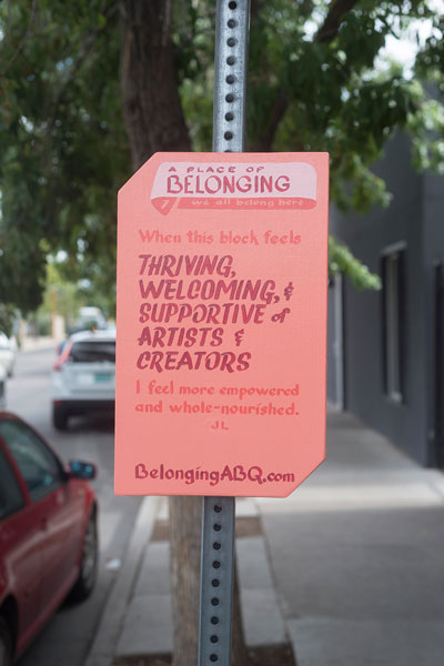 "Sign reads, ""A place of belonging #1, We all belong here. When this block feels thriving, welcoming, and supportive of artists and creators, I feel more empowered and whole-nourished. JL BelongingABQ.com."" Salmon colored sign on a post on a sidewalk with trees and parked cars in the background."