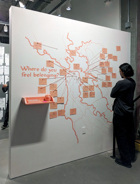 "Wall painted with map of bay area in salmon colored paint, with the text ""Where do you feel belonging?"" There's cards on the map with yarn and pins to different locations. There's a pink shelf with yard, scissors and pins. A visitor is close, reading the cards."