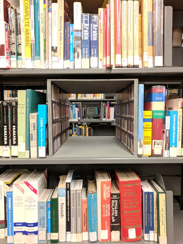 A view of Passage, a portal of perfectly-lined up boxes that create a negative space through the library book shelves.