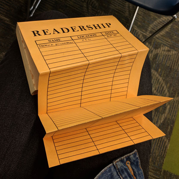 "A book with a fold-out back cover. It looks like an inter-office envelope, but the top says ""readership,"" and the table headers say, ""Name, location, date."""