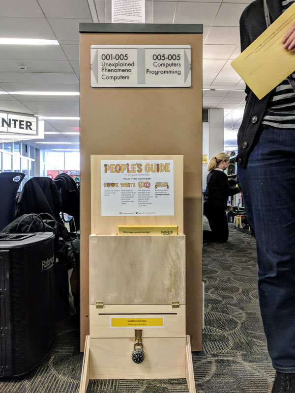 Wooden display holding forms and a submission box, located at the end of stacks of library books.