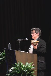 Person holding a bowl in one hand, standing at a podium.