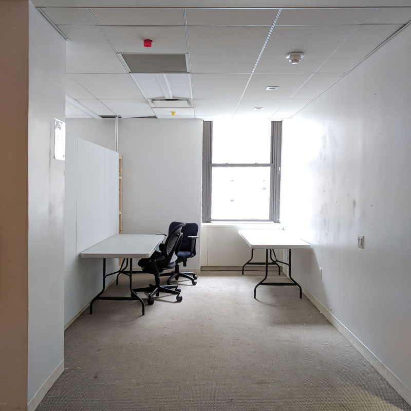 A empty white walled room with a bright window in the back corner. Two tables and two office chairs. light brown carpet.
