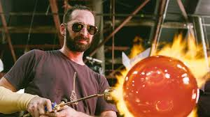 A man wearing sunglasses using a gas torch on a molten ball of glass.