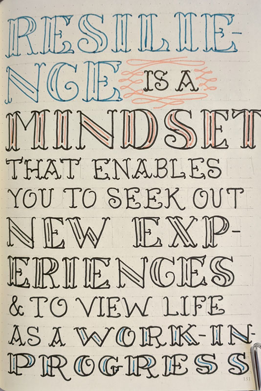 Fancy handlettering on a dot grid sketchbook page in pink, blue and black marker. Text reads: Resilience is a mindset that enables you to seek out new experiences and to view life as a work in progress.