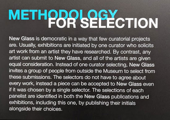 "Signage that states, ""Methodology for Selection. New Glass is democratic in a way that few curatorial projects are. Usually, exhibitions are initiated by one curator who solicits art work from an artist they have researched. By contrast, any artist can submit to New Glass, and all of the artists are given equal consideration. Instead of one curator selecting, New Glass invites a group of people from outside the Museum to select from these submissions. The selectors do not have to agree about every work, instead a piece can be accepted to New Glass even if it was chosen by a single selector. The selections of each panelist are identified in both the New Glass publications and exhibitions, including this one, by publishing their initials alongside their choices."""
