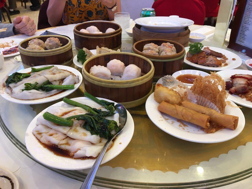 A photo of diners around a glass lazy Susan loaded with dim sum dishes: rice rolls, chinese broccoli (gai lan), spring rolls, deep fried taro dumplings, shrimp dumplings (har gow), beef dumplings (siu mai), roast pork, roast duck