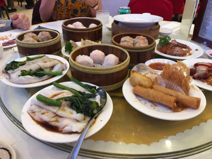 A photo of diners around a glass lazy Susan loaded with dim sum dishes: rice rolls, chinese broccoli (gai lan), spring rolls, deep fried taro dumplings, shrimp dumplings (har gow), beef dumplings (siu mai), roast pork, roast duck