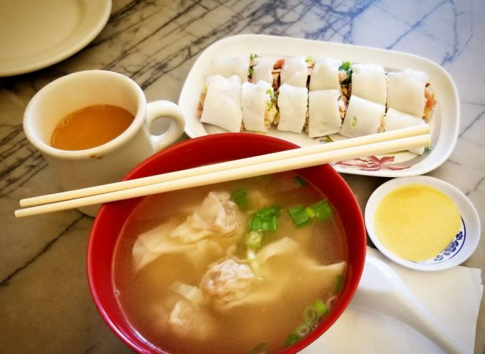 Photo of a red bowl with broth and wontons. A mug with possibly HK style milk tea, and a rice roll with a side of mustard.