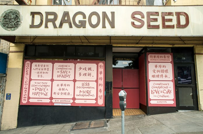 """Photo of Dragon Seed Bridal and Photography storefront. A big sign above reads, """"Dragon Seed"""" in brown text on white background. Below, the window is boarded up and covered in a wheatpasted poster. The text on the poster is in English and Chinese. It reads: Hopes for Chinatown. To see people living and working in peace and harmony, by Alina. Everyone in Chinatown will be safe and healthy. Anonymous. Less discrimination. More Understanding. YY. Chinatown's Generations of love and care will continue. Sunflower. The text is in red in light pink boxes on a background of red with a scale-like pattern of overlapping concentric circles."""