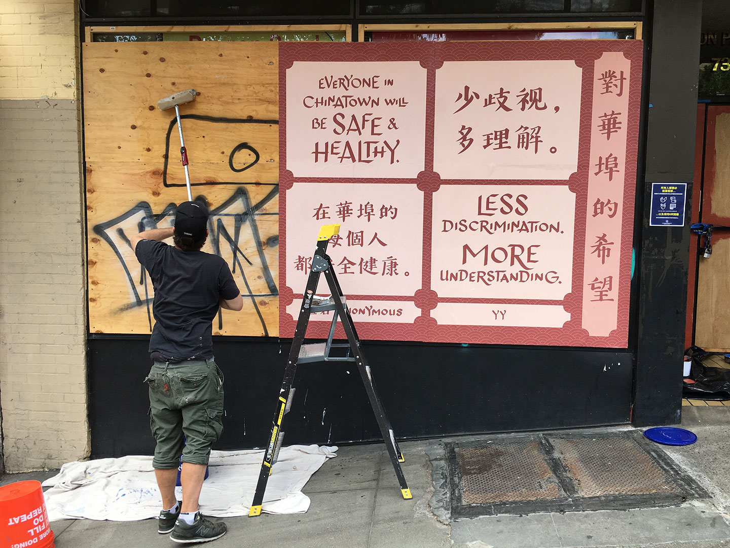 Photo of artwork being installed on graffiti-covered plywood covering storefront windows.