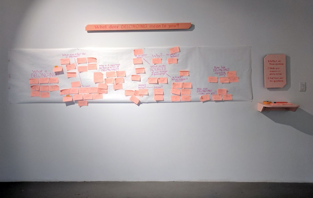 "A photo of a gallery wall with a piece of paper with questions about belonging in it. There are also salmon pink signs that say ""What does belonging mean to you?"""