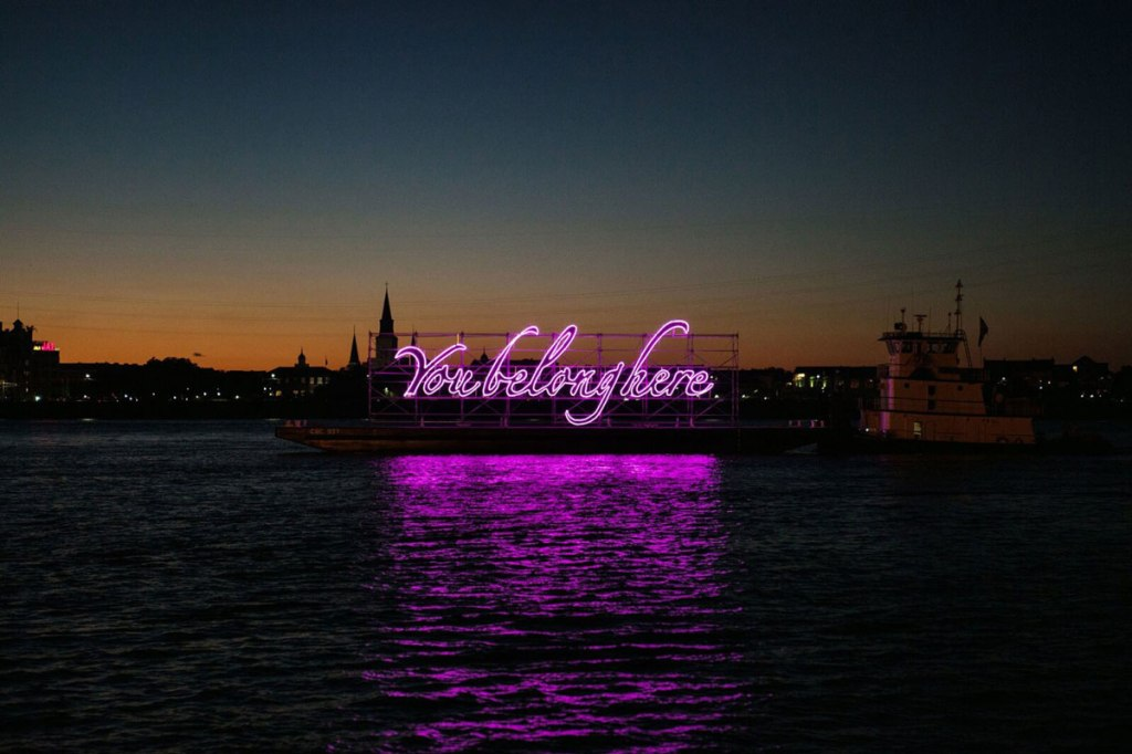 a photo of a neon installation with the text, 'You belong here' in puruple script.' the neon is installed on a waterfront, so it reflects in the water. The photo was taken after sunset.